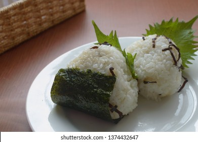 a plate of Japanese rice balls with salted kelp