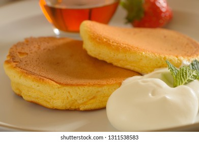 a plate of Japanese souffle pancake with fresh strawberries and maple syrup