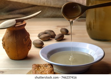 a plate and a jar of honey, wooden spoon dripping with honey, wooden table and nuts