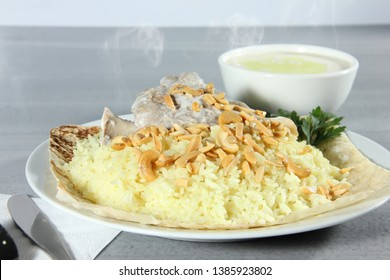 A plate of Jordanian Mansaf  (Bread, Rice, Lamb meat) dressed with nuts and parsley, a bowl of Yogurt soup (Jameed)  in the back.