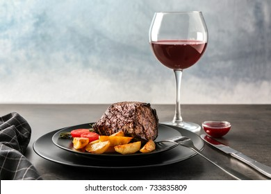 Plate with juicy steak and glass of wine on table against light background