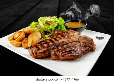 Plate with juicy thick angus stake, bowl of steaming red sauce, golden french fries and green vegetables. Studio shot with black wooden background.