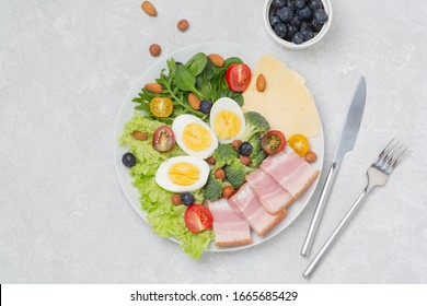 Plate with keto diet food. Keto breakfast: eggs, cheese, brisket, lettuce, broccoli, spinach, arugula, almonds, hazelnuts, blueberries and tomatoes.