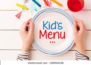 Plate with 'Kid's Menu' sign in child's hands. White planked wooden background with colorful decorations. Table setting for children - captured from above (top view, flat lay).