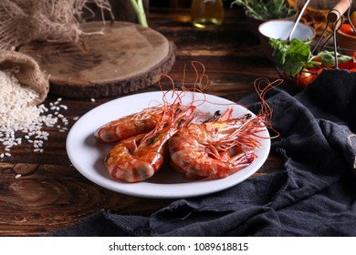 Plate of king size red King Prawns served on wooden table in a rustic kitchen.