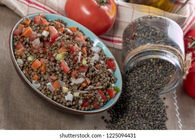 a plate of lentil salad with tomatoes and onions