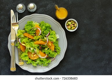 A plate of lettuce, with slices of orange, red onion, with vinaigrette dressing.