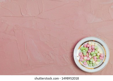 Plate of Marshmallows on pink background. Colorful marshmallow sweets with copy space. View from above or top view