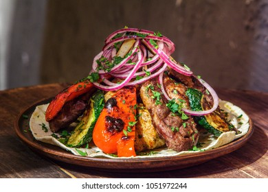 plate with meat kebab, herbs, species, onion rigs on pita bread on wooden table. plate for company.