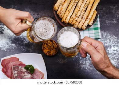 Plate with meat, salted peanuts and cheese sticks to beer. Two glasses with light beer in male hands, drinking in the pub with a friend.