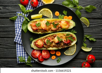 Plate with meat stuffed zucchini boats and vegetables on wooden table