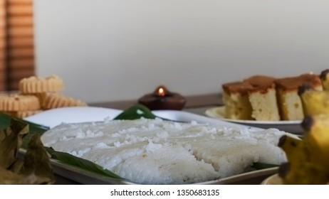 Plate of Milk Rice (Kiribath) along with a lit Oild Lamp, Kokis, Cake & Banana in the background & foreground  - A New Year Festival food in Sri Lanka. Also known as Sinhala & Tamil Avurudhu Sweets