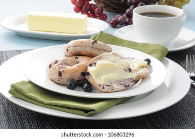 A plate of mini blueberry bagels with a cup of coffee