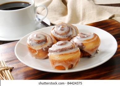 A plate of mini cinnamon rolls and a cup of black coffee