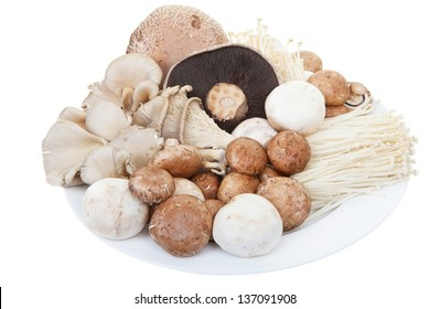A plate of mixed mushrooms on a white background