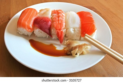 A plate of mixed seafood nigiri sushi sits on a white plate with chopsticks, pickled ginger and soy sauce