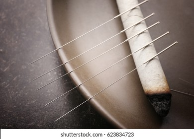Plate with moxa stick and needles for acupuncture on dark textured background, closeup