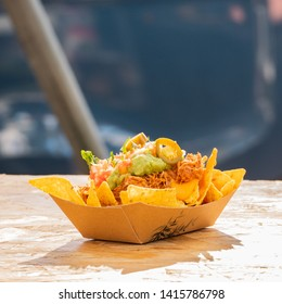 plate of nachos with ground meat and salsa topped with cheese mexican food truck on festival