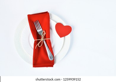 Plate with a napkin and a red heart on a white background, Valentine's Day