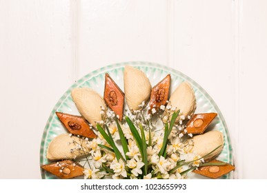 Plate with national sweets pastry for Novruz celebration in Azerbaijan, shekerbura and pakhlava with fresh green wheatgrass semeni and flowers, copy space light grey background