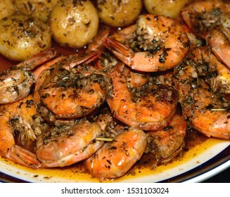 A plate of New Orleans style Bar-B-Que Shrimp with New Potatoes, shallow depth of field.