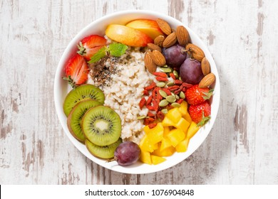 plate of oatmeal porridge with fresh fruit and superfoods, top view, closeup