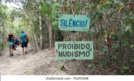 Plate on a trail inside a forest with information of Silence and Forbidden nudism, written in Portuguese.