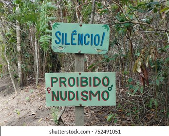 Plate on a trail inside a forest with information of Silence and Forbidden nudism, written in Portuguese