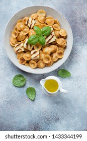 Plate of orecchiette pasta with slices of grilled cheese, sun dried tomato pesto and fresh green basil. Top view on a light-grey stone background