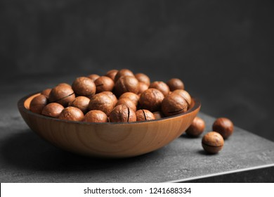Plate with organic Macadamia nuts on table against dark background. Space for text