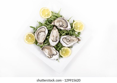 plate with oyster, lemon slices and wild rocket salad