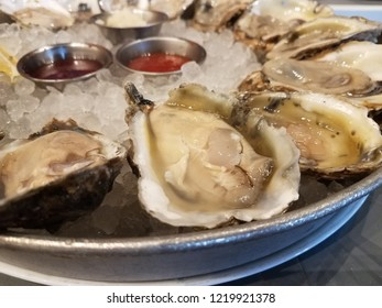 plate of oysters on ice with dipping sauces