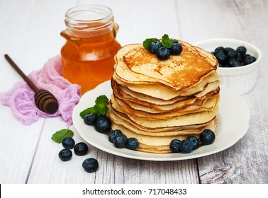 Plate with pancakes and blueberries on a table