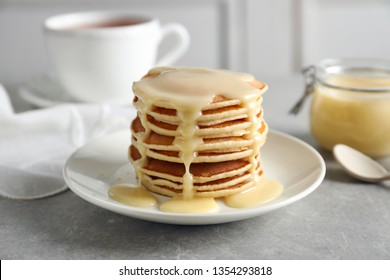 Plate with pancakes and condensed milk served on table. Dairy product