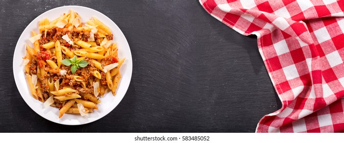 plate of pasta bolognese on dark table, top view