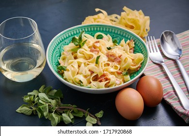 Plate of pasta carbonara with a glass of white wine on a dark wooden table