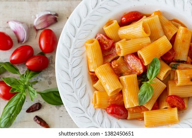 A plate with pasta with cherry tomatoes and basil from above. At the side: garlic, tomatoes, red chilly pepper and basil.