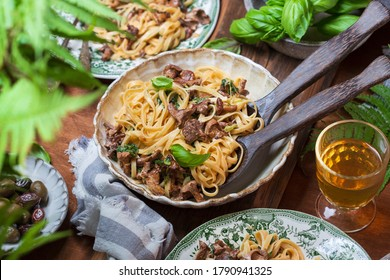 Plate of pasta with forest chanterelles and green basil