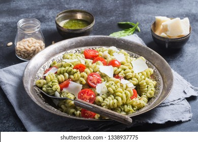 Plate of pasta with italian pesto sauce on dark chalkboard background. Horizontal orientation