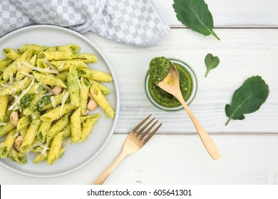 Plate of pasta and pesto of radish green on an old white wooden background
