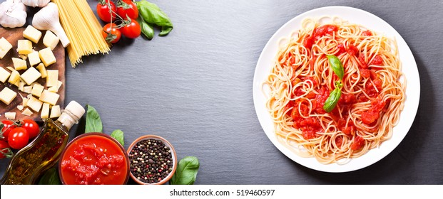 plate of pasta with tomato sauce with ingredients for cooking on dark background, top view with copy space
