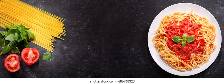 plate of pasta with tomato sauce and ingredients for cooking on dark background, top view