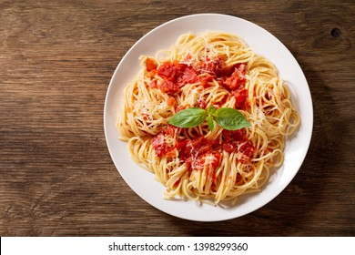 plate of pasta with tomato sauce on wooden table, top view
