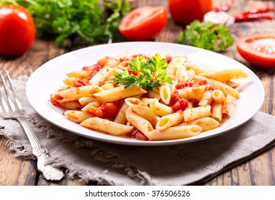 plate of pasta with tomato sauce on wooden table