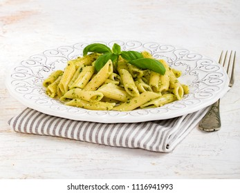 Plate of pasta type penne rigate with basil pesto, on white background.