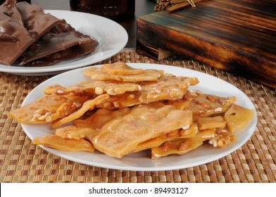 A plate of peanut brittle and chocolates in the background