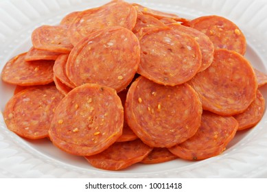 A plate of pepperoni ready for the pizza or a salad.