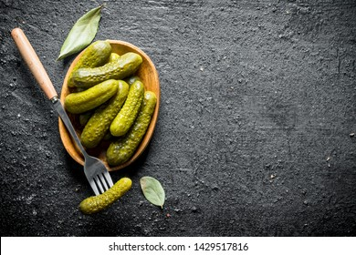 Plate of pickled homemade cucumbers. On black rustic background