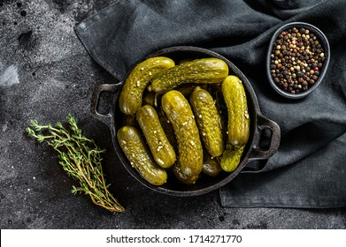 Plate of pickled homemade cucumbers, pickles. Black background. Top view