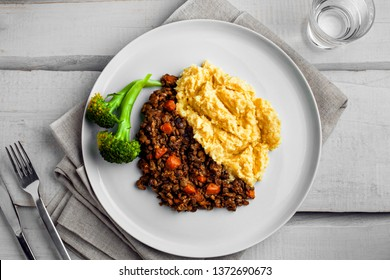 Plate of shepherd's pie on a white wooden table. Meal made of smashed potatoes, minced meat, lentil and vegetables. Top view, above shot.